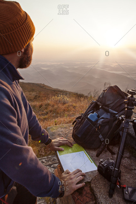 Man looking away while standing with map on observation point