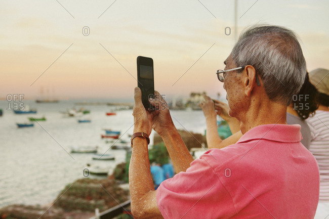 Senior man photographing through smart phone while standing with siblings at harbor