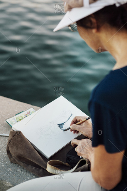 Cropped image of woman painting on paper while resting at retaining wall by sea