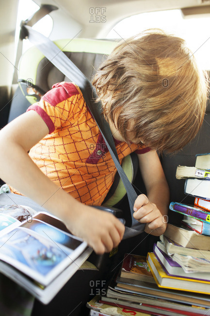 Girl with books tying seat belt while sitting in car