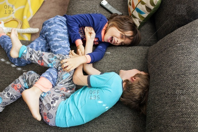 Overhead view of siblings playing on sofa at home