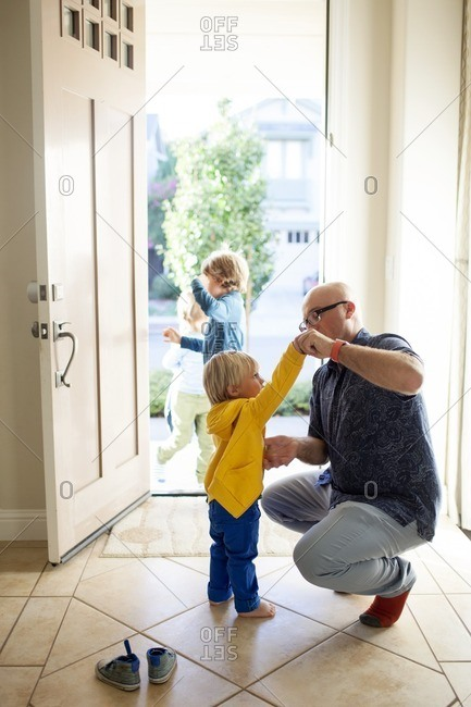 Father dressing up son while boys standing at entrance
