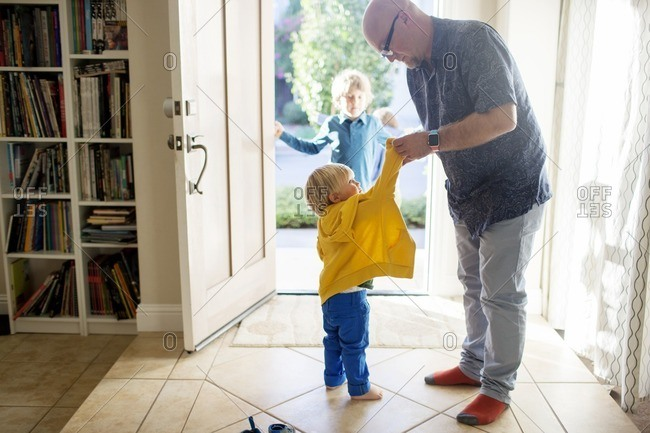 Father dressing up son while standing at home