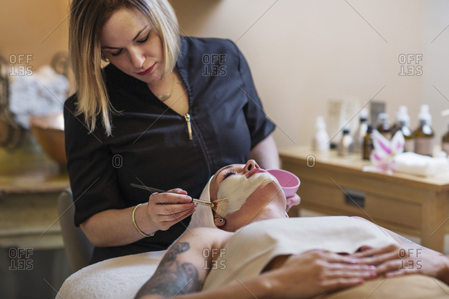 Beautician applying face mask to woman in spa