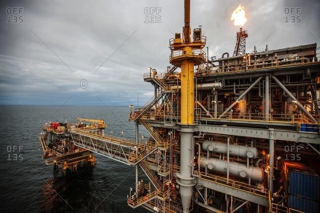 Oil rig in sea emitting fire