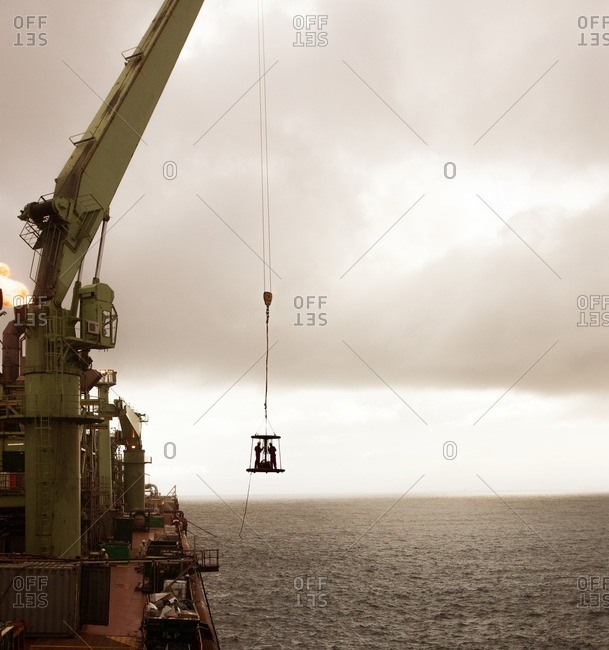 Workers on platform hanging by crane over sea