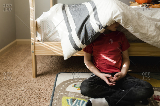 Boy sitting against bunk bed with blanket on head