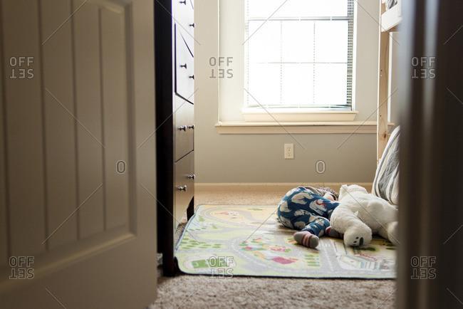 Boy sleeping with teddy bear on mat at home