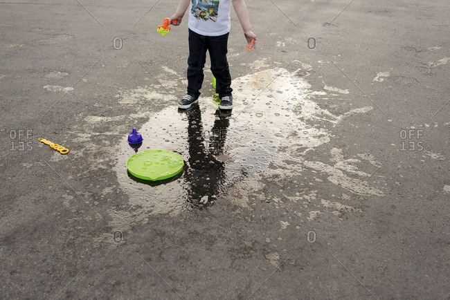 Low section of boy with toys standing on wet road