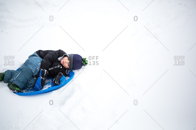 Boy lying in saucer-shaped sled
