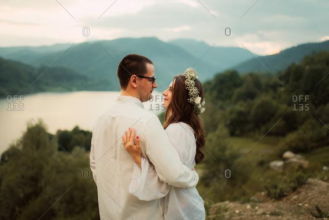 Bridal couple hugging by valley vista