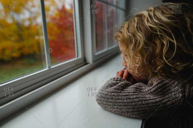 Boy staring out window into fall yard