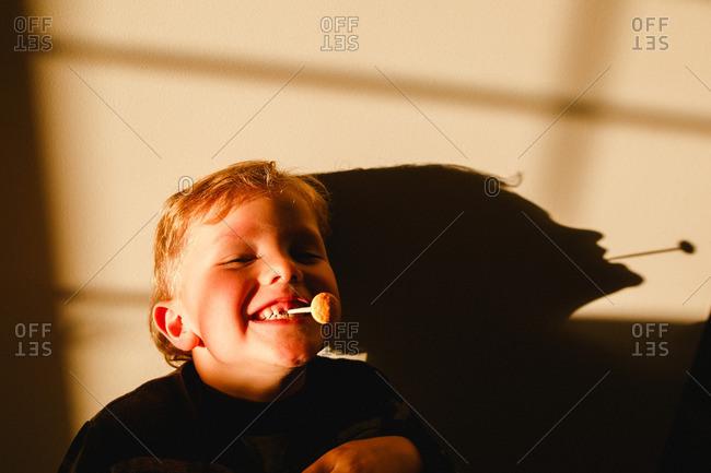 Boy with lollipop in teeth