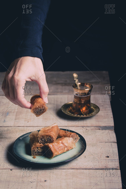 Woman's hand holding a sweet pastry on a rustic table
