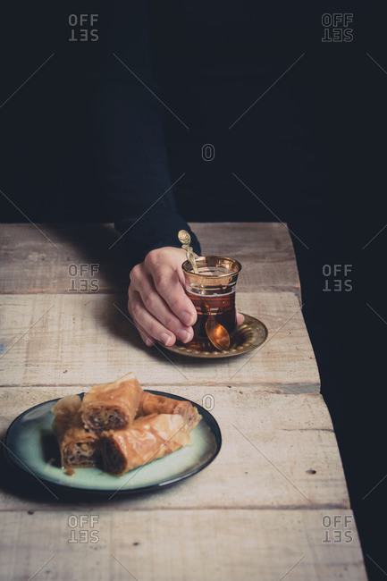 Woman's hand holding cup of tea with sweet pastry on a rustic table