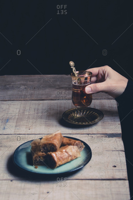 Woman's hand holding tea by a sweet pastry on a rustic table