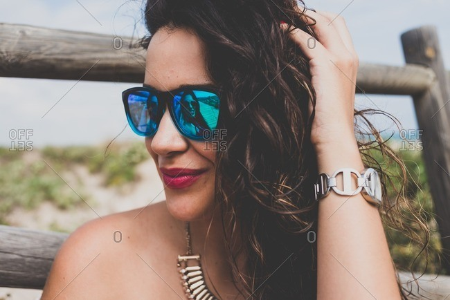 Reflection of young woman in her friend's sunglasses