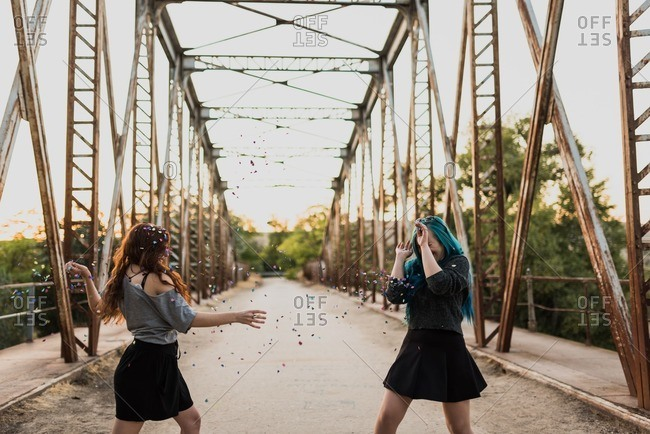 Two teen girls throwing confetti at one another on a bridge