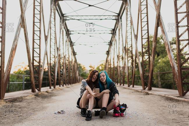 Two teenage girls sitting on skateboard on a bridge taking a selfie