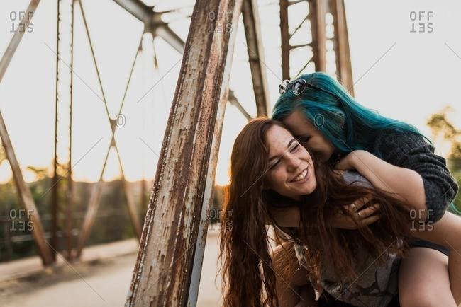 Teen girl giving her friend a piggy back ride on a bridge