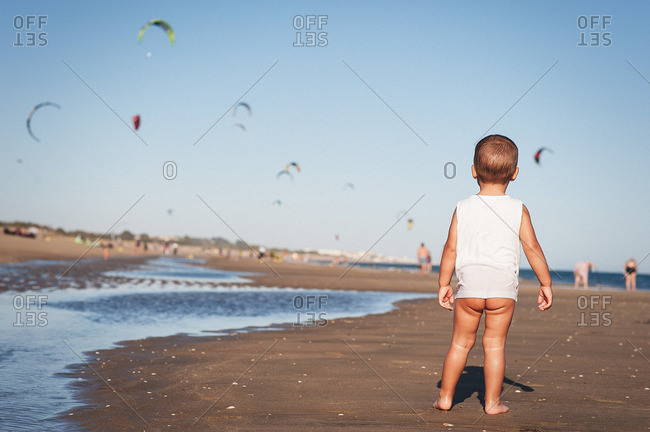 Back view of baby with naked bottom standing on beach watching flying parachutes
