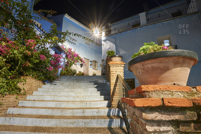 Blue buildings and steps with pink flowers in the village of Juzcar, Spain