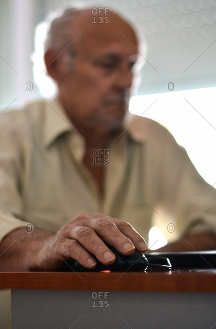 Close up of an elderly man's hand using mouse and laptop at home