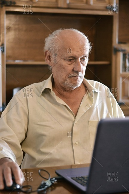 Senior man using a laptop at home