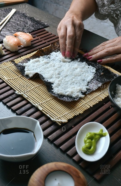 Woman preparing sushi rolls with rice at home