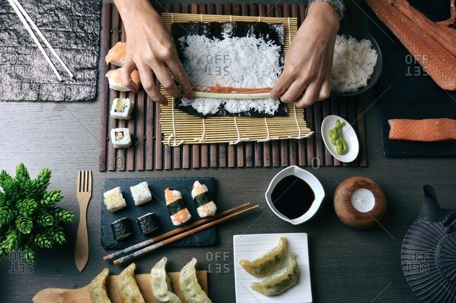 Woman preparing sushi rolls with salmon and cucumber at home
