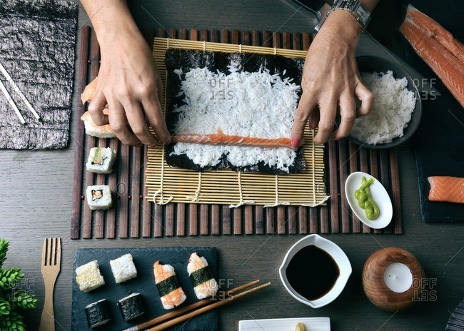 Woman preparing sushi rolls with salmon at home