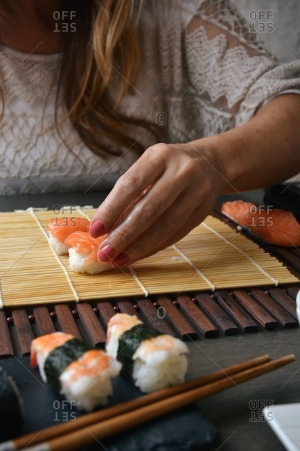 Woman placing salmon and rice on a mat for sushi rolls