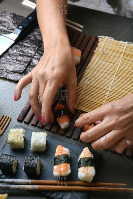 Woman preparing sushi rolls with rice and salmon at home