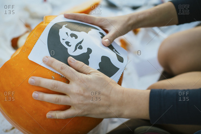 Person placing paper with ghost on a pumpkin