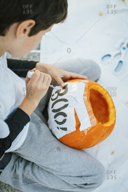 "Boy carves ""Boo!"" text on Halloween pumpkin with knife. Using paper print as stencil."