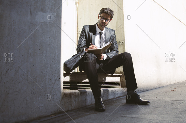 Stylish businessman in spectacles and black suit writing in notebook while sitting on stairs