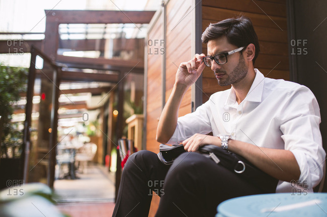 Stylish businessman sitting with briefcase and touching spectacles