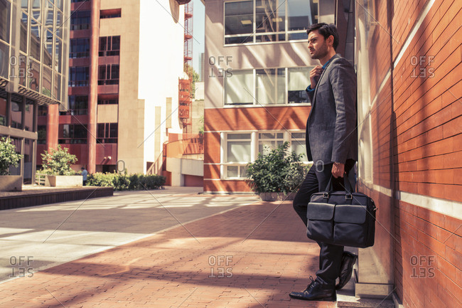 Side view of bearded businessman with briefcase against of modern city building