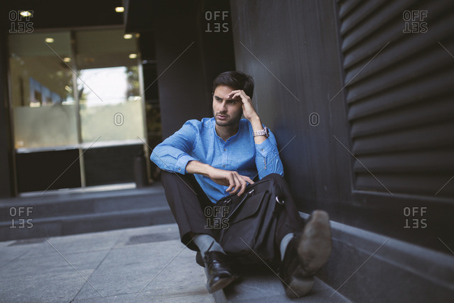 Portrait of depressed businessman in blue shirt sitting on ground beside wall with briefcase