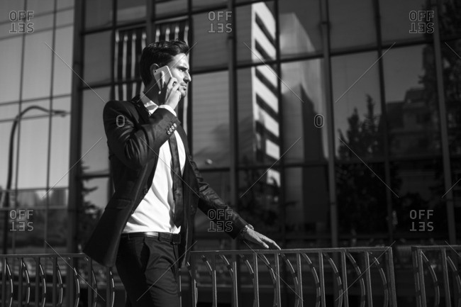 Side view of handsome stylish businessman talking on the phone while walking on a city street