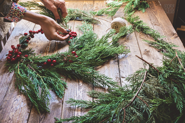 Florist making a wreath with red berries and branches