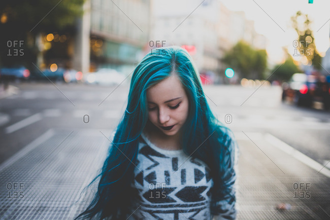 Sad punk girl with blue hair walking on a city street