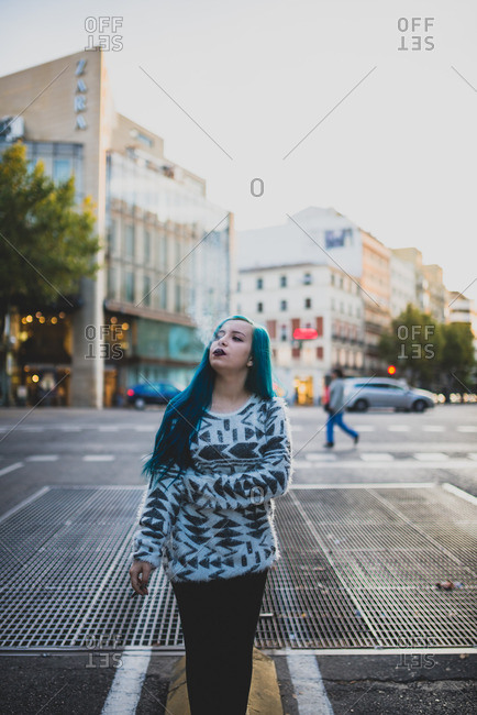 Punk girl with blue hair walking on city street smoking a cigarette