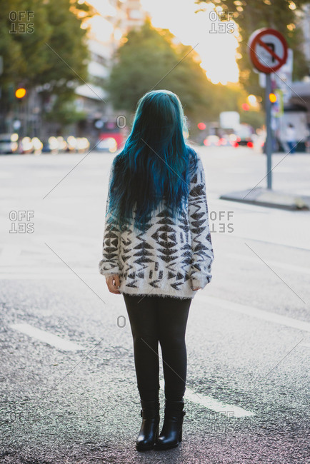 Young punk girl standing with her head down and hair hide her face.