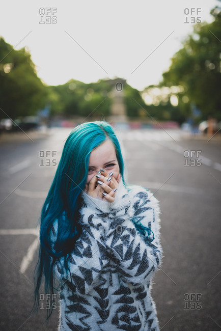 Happy punk girl with blue hair covering her mouth while standing on a city street