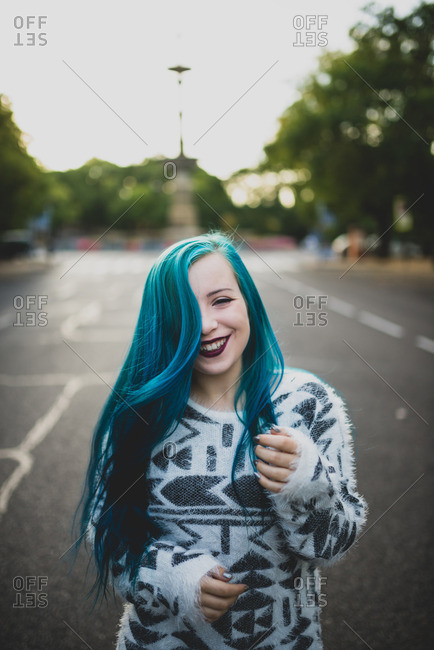 Happy punk girl with blue hair on a city street
