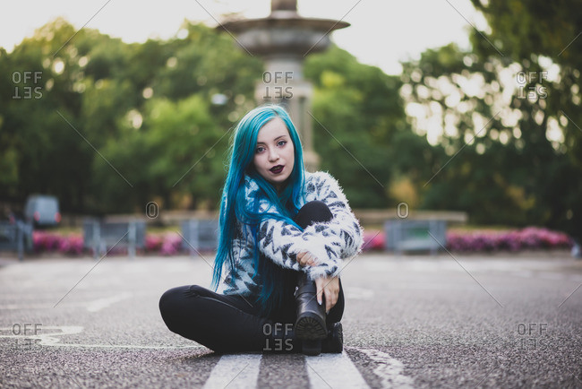 Punk girl with blue hair sitting on city street