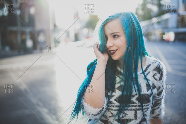 Blue haired punk girl looking away while standing on a city street