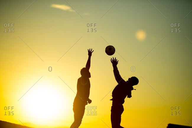 Two young men jumping up for a basketball at sunset