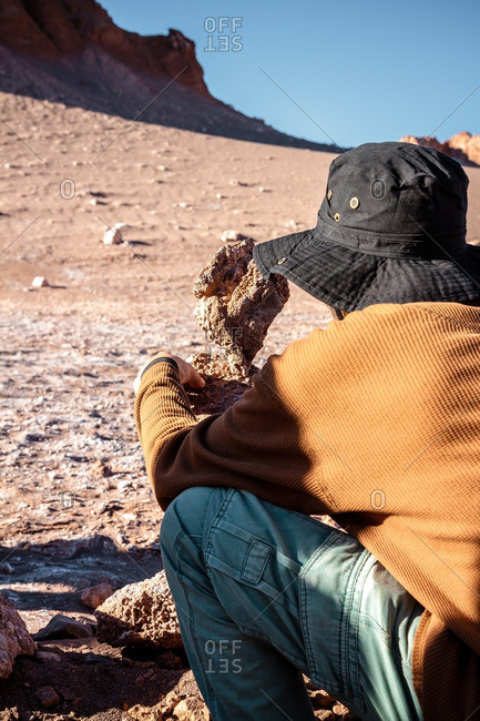 Man touching a rock formation in the Valley of the Moon in the Atacama desert, Chile